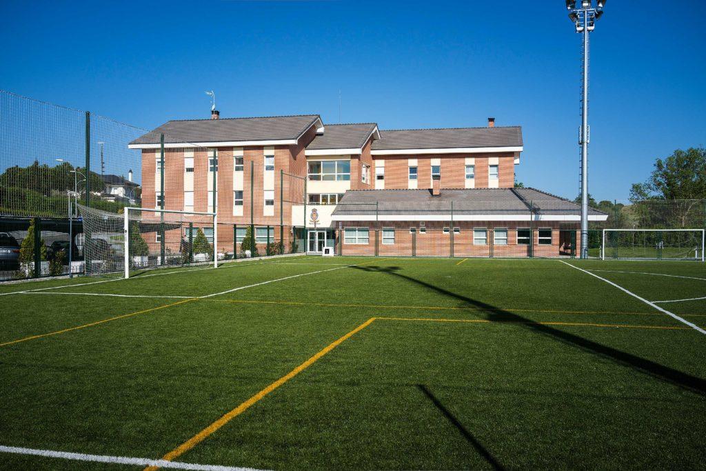 Foto des King's College in Madrid. Sie sehen die orangefarbene Fassade der Schule zusammen mit einem grünen Kunstrasen-Fußballfeld, das sich auf dem Campus befindet.