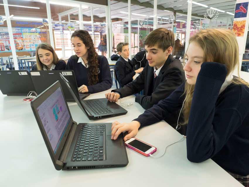 gruppe von schülern um einen computer in der sek el castillo schule