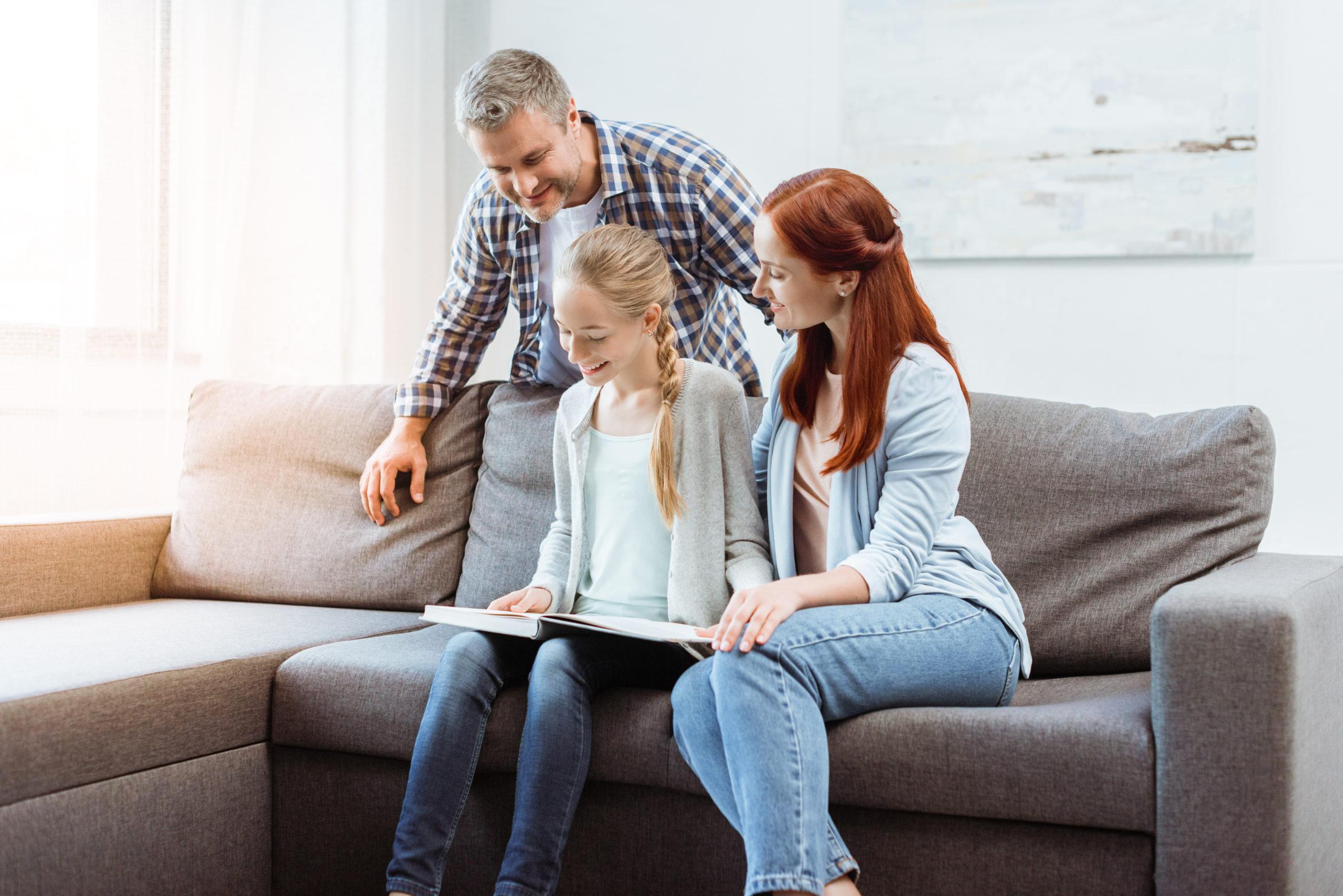 glückliche Eltern und Teenager-Mädchen lesen Buch zusammen