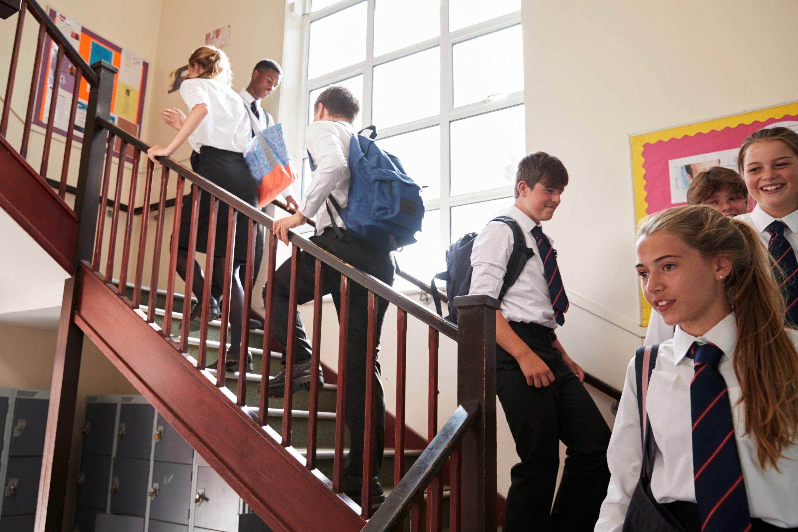 FAQ-Seitenbanner, das eine Gruppe von Schülern zeigt, die in Schuluniform die Treppe hinuntergehen