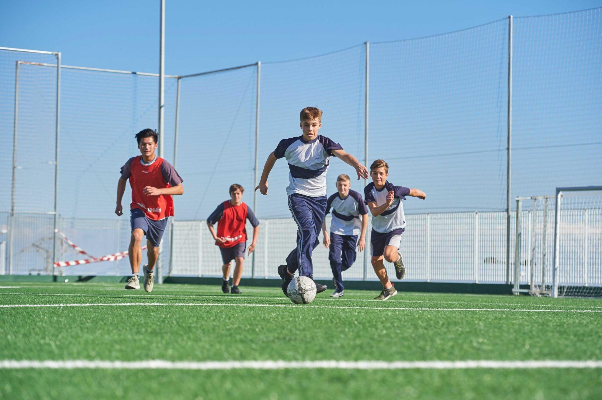Kinder-spielen- Fußball-auf-dem-Rasen-in-der- Schule